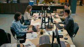 Η επιχειρηματική μονάδα των περιστασιακών ανθρώπων εργάζεται στους υπολογιστές στο γραφείο ανοιχτού χώρου απόθεμα βίντεο