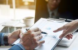 Η επιχειρηματική μονάδα που συζητά τα στοιχεία σχεδιάζει τα έγγραφα Στοκ εικόνες με δικαίωμα ελεύθερης χρήσης