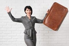 Η επιχειρησιακή γυναίκα έντυσε σε ένα γκρίζο κοστούμι με την παραμονή βαλιτσών μπροστά από έναν άσπρο τοίχο στοκ εικόνες με δικαίωμα ελεύθερης χρήσης