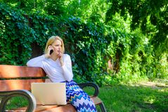 Η επιχειρησιακή γυναίκα απασχολείται στο πάρκο με το smartphone lap-top Η κλήση smartphone κοριτσιών λύνει το επιχειρησιακό πρόβλ Στοκ φωτογραφία με δικαίωμα ελεύθερης χρήσης
