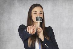 Η επιχειρησιακή γυναίκα καλύπτει το στόμα της με ένα σημάδι δολαρίων, δείχνοντας το Υ Στοκ Εικόνες