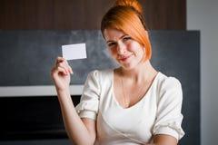 Η επιχειρησιακή γυναίκα κρατά μια επαγγελματική κάρτα μέσα στο γραφείο Στοκ φωτογραφίες με δικαίωμα ελεύθερης χρήσης