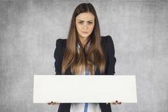 Η επιχειρησιακή γυναίκα κρατά μια θέση για την αγγελία σας, που στέκεται στο γκρίζο υπόβαθροη Στοκ Εικόνες