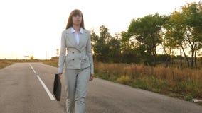 Η επιχειρησιακή γυναίκα με έναν μαύρο χαρτοφύλακα περπατά στο ελαφρύ κοστούμι και τους άσπρους ψηλοτάκουνους περιπάτους παπουτσιώ φιλμ μικρού μήκους