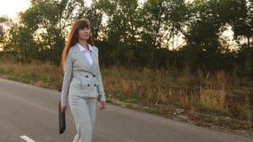 Η επιχειρησιακή γυναίκα με έναν μαύρο χαρτοφύλακα περπατά στο ελαφρύ κοστούμι και τους άσπρους ψηλοτάκουνους περιπάτους παπουτσιώ απόθεμα βίντεο