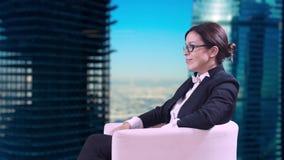 Η επιχειρησιακή γυναίκα με τα γυαλιά που κάθεται στο στούντιο σε ένα επιχειρησιακό κοστούμι και δίνει τις συνεντεύξεις Στο υπόβαθ απόθεμα βίντεο