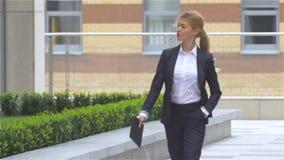 Η επιχειρησιακή γυναίκα με τον υπολογιστή ταμπλετών πηγαίνει γύρω από το κτίριο γραφείων κίνηση αργή φιλμ μικρού μήκους