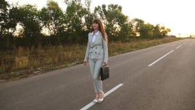 Η επιχειρησιακή γυναίκα με τους μαύρους περιπάτους χαρτοφυλάκων στο ελαφρύ κοστούμι και τα άσπρα ψηλοτάκουνα παπούτσια πηγαίνει έ φιλμ μικρού μήκους