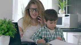 Η επιχειρησιακή γυναίκα με το γιο στα χέρια κάνει το μέρος της εργασίας με το lap-top και το τηλέφωνο ταυτόχρονα απόθεμα βίντεο