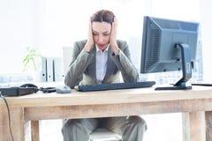 Η επιχειρησιακή γυναίκα με το κεφάλι παραδίδει μέσα το μέτωπο του υπολογιστή στο γραφείο Στοκ Φωτογραφία