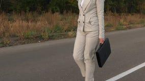 Η επιχειρησιακή γυναίκα με το μαύρο χαρτοφύλακα στο χέρι της, πηγαίνει στο παντελόνι και το σακάκι στην άσφαλτο έξω από την πόλη, φιλμ μικρού μήκους