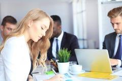 Η επιχειρησιακή γυναίκα με το προσωπικό της, άνθρωποι ομαδοποιεί στο υπόβαθρο στο σύγχρονο φωτεινό γραφείο στο εσωτερικό στοκ φωτογραφίες με δικαίωμα ελεύθερης χρήσης