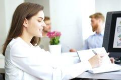 Η επιχειρησιακή γυναίκα με το προσωπικό της, άνθρωποι ομαδοποιεί στο υπόβαθρο στο σύγχρονο φωτεινό γραφείο στο εσωτερικό στοκ εικόνα