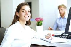 Η επιχειρησιακή γυναίκα με το προσωπικό της, άνθρωποι ομαδοποιεί στο υπόβαθρο στο σύγχρονο φωτεινό γραφείο στο εσωτερικό στοκ φωτογραφία με δικαίωμα ελεύθερης χρήσης