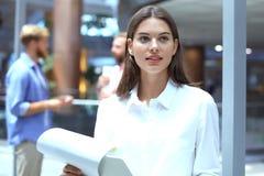Η επιχειρησιακή γυναίκα με το προσωπικό της, άνθρωποι ομαδοποιεί στο υπόβαθρο στο σύγχρονο φωτεινό γραφείο στοκ εικόνες με δικαίωμα ελεύθερης χρήσης