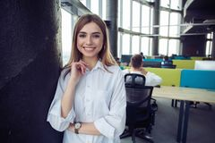 Η επιχειρησιακή γυναίκα με το προσωπικό της, άνθρωποι ομαδοποιεί στο υπόβαθρο στο σύγχρονο φωτεινό γραφείο στο εσωτερικό στοκ εικόνες