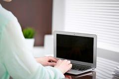 Η επιχειρησιακή γυναίκα παραδίδει μια πράσινη συνεδρίαση μπλουζών στο γραφείο στο γραφείο και τη δακτυλογράφηση στο lap-top Στοκ Φωτογραφίες