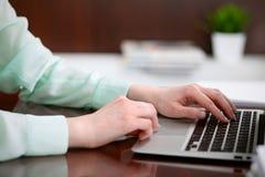 Η επιχειρησιακή γυναίκα παραδίδει μια πράσινη συνεδρίαση μπλουζών στο γραφείο στο γραφείο και τη δακτυλογράφηση στο lap-top Στοκ Εικόνες