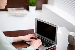 Η επιχειρησιακή γυναίκα παραδίδει μια πράσινη συνεδρίαση μπλουζών στο γραφείο στο γραφείο και τη δακτυλογράφηση στο lap-top Στοκ εικόνες με δικαίωμα ελεύθερης χρήσης