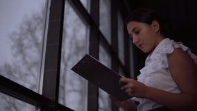 Η επιχειρησιακή γυναίκα περπατά επάνω στα επιχειρησιακά έγγραφα εκμετάλλευσης παραθύρων στα χέρια της απόθεμα βίντεο