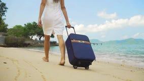 Η επιχειρησιακή γυναίκα περπατά κατά μήκος της ακτής μιας όμορφης θάλασσας με μια βαλίτσα ανεξάρτητη έννοια, αναμενόμενη για καιρ απόθεμα βίντεο