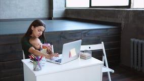 Η επιχειρησιακή γυναίκα που κρατά ένα χέρι μωρών ` s εργάζεται στο γραφείο στον υπολογιστή φιλμ μικρού μήκους