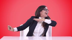 Η επιχειρησιακή γυναίκα σε μια συνεδρίαση επιχειρησιακών κοστουμιών πίσω από ένα γραφείο και απολαμβάνει πολύ Κόκκινη ανασκόπηση απόθεμα βίντεο