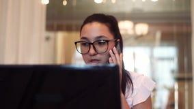 Η επιχειρησιακή γυναίκα στα γυαλιά εργάζεται χρησιμοποιώντας τον υπολογιστή και την κινητή τηλεφωνική συνεδρίαση στον πίνακα στην απόθεμα βίντεο