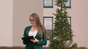 Η επιχειρησιακή γυναίκα στα γυαλιά και το επιχειρησιακό κοστούμι γράφει κάτι στα έγγραφα απόθεμα βίντεο