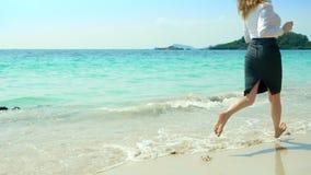 Η επιχειρησιακή γυναίκα στα ενδύματα γραφείων τρέχει χωρίς παπούτσια στη θάλασσα κατά μήκος μιας άσπρης αμμώδους παραλίας ανεξάρτ στοκ φωτογραφία με δικαίωμα ελεύθερης χρήσης