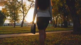 Η επιχειρησιακή γυναίκα στη φούστα περπατά στο πάρκο στις ακτίνες του όμορφου ηλιοβασιλέματος με τα μαύρα έγγραφα χαρτοφυλάκων απόθεμα βίντεο