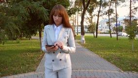 Η επιχειρησιακή γυναίκα στο επιχειρησιακό κοστούμι με την ταμπλέτα διαθέσιμη περπατά στο πάρκο βραδιού που περνά το ελεύθερο χρόν φιλμ μικρού μήκους