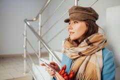 Η επιχειρησιακή γυναίκα στο παλτό στέκεται στα σκαλοπάτια στη λεωφόρο με το smartphone Αγορές Μόδα στοκ φωτογραφίες με δικαίωμα ελεύθερης χρήσης