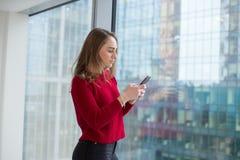 Η επιχειρησιακή γυναίκα στο παράθυρο παρουσιάζει ένα δάχτυλο και μιλά στο τηλέφωνο τηλεφωνικές διαπραγματεύσεις και έγκριση του α στοκ φωτογραφία με δικαίωμα ελεύθερης χρήσης