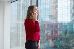 Η επιχειρησιακή γυναίκα στο παράθυρο παρουσιάζει ένα δάχτυλο και μιλά στο τηλέφωνο τηλεφωνικές διαπραγματεύσεις και έγκριση του α στοκ φωτογραφία