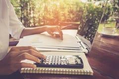 Η επιχειρησιακή γυναίκα υπολογίζει και αναλύοντας το έγγραφο γραφικών παραστάσεων οικονομικό με τον εκλεκτής ποιότητας τόνο lap-t Στοκ φωτογραφίες με δικαίωμα ελεύθερης χρήσης