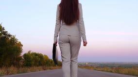 Η επιχειρησιακή γυναίκα φέρνει το μαύρο χαρτοφύλακα με τα έγγραφα στο αριστερό χέρι της, άποψη από την πλάτη φιλμ μικρού μήκους
