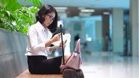 Η επιχειρησιακή γυναίκα χρησιμοποιεί την ταμπλέτα στο σταθμό τρένου φιλμ μικρού μήκους