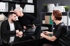 Η επιχειρησιακή γυναίκα ψιθυρίζει κάτι στον άνδρα στο αυτί με ένα άλλο νέο κορίτσι στοκ εικόνες