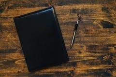 Η επιχειρησιακή ημερήσια διάταξη σημειωματάριων σχεδίου με το δέρμα καλύπτει τη τοπ άποψη Στοκ εικόνες με δικαίωμα ελεύθερης χρήσης