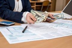 Η επιχειρησιακή κυρία μετρά τα δολάρια, πέρα από τη φορολογική μορφή 1040 στοκ φωτογραφία με δικαίωμα ελεύθερης χρήσης
