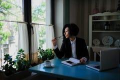 Η επιχειρησιακή κυρία με τα γυαλιά έντυσε στο μαύρο κοστούμι που λειτουργεί σε ένα Λα Στοκ εικόνες με δικαίωμα ελεύθερης χρήσης