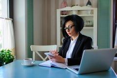 Η επιχειρησιακή κυρία με τα γυαλιά έντυσε στο μαύρο κοστούμι που λειτουργεί σε ένα Λα Στοκ Φωτογραφία