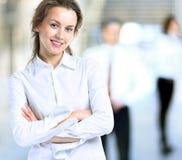 Η επιχειρησιακή κυρία με το θετικό κοιτάζει και εύθυμη τοποθέτηση χαμόγελου Στοκ Φωτογραφίες