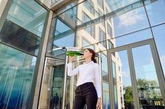 Η επιχειρησιακή κυρία πίνει το νερό από ένα πλαστικό μπουκάλι στο backgrou Στοκ Εικόνες