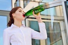 Η επιχειρησιακή κυρία πίνει το νερό από ένα πλαστικό μπουκάλι στο backgrou Στοκ φωτογραφία με δικαίωμα ελεύθερης χρήσης