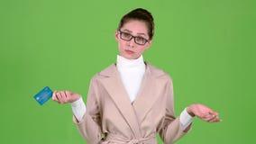 Η επιχειρησιακή κυρία που κρατά μια πιστωτική κάρτα στα χέρια της δεν έχει κανένα χρήμα πράσινη οθόνη κίνηση αργή φιλμ μικρού μήκους