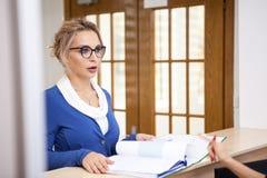 Η επιχειρησιακή κυρία στην αναμονή εξετάζει το γραμματέα Στοκ Εικόνα