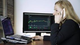 Η επιχειρησιακή κυρία συμβουλεύει τον πελάτη για ένα τηλέφωνο και το διάγραμμα ανταλλαγής νομίσματος προσοχής στο όργανο ελέγχου  φιλμ μικρού μήκους