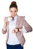 Η επιχειρησιακή κυρία τελειώνει τον καφέ της και εξετάζει το ρολόι Στοκ φωτογραφία με δικαίωμα ελεύθερης χρήσης